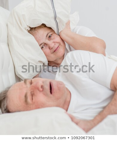 Photo stock: Woman Blocking Ears With Fingers While Husband Snoring