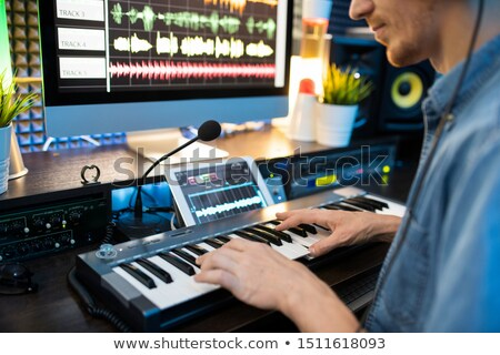 Young musician sitting by workplace and pressing keys of piano keyboard Stock photo © pressmaster