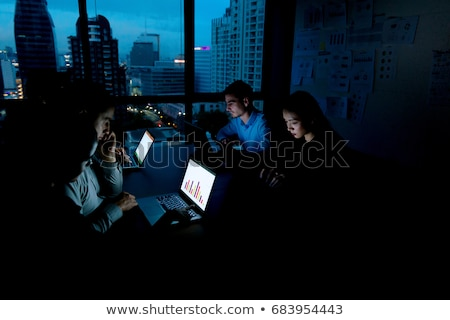 business team with papers working at night office stock photo © dolgachov