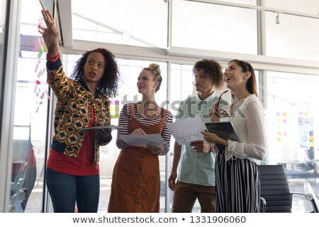 Low angle front view of multi-ethnic business colleagues discussing plans over sticky notes in moder Stock photo © wavebreak_media