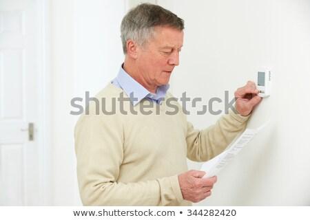 Starszy człowiek centralny ogrzewania termostat szczęśliwy Zdjęcia stock © HighwayStarz