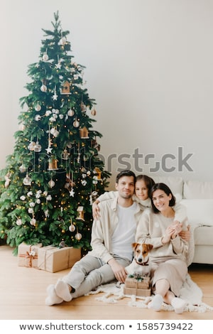 Three family members pose on floor in cozy room, gift boxes around, decorated New Year tree and sofa Stock photo © vkstudio
