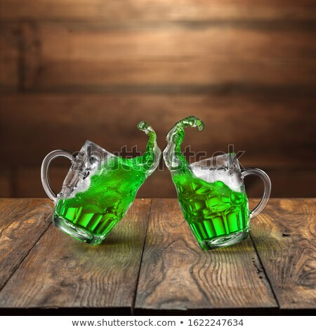 Two bouncing beer mugs with green drink splashes. Stock photo © artjazz