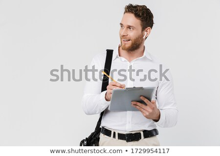 Portrait of happy handsome man using earphones and holding clipboard Stock photo © deandrobot