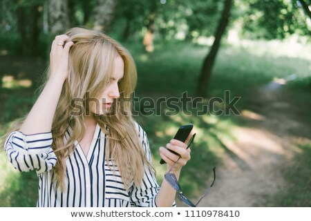 Horizontal shot of pretty female with wavy hair, has blue eyes, dressed in elegant blouse, poses on  Stock photo © vkstudio