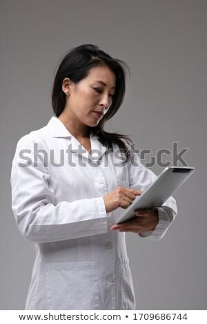 Dedicated Asian nurse or doctor checking notes Stock photo © Giulio_Fornasar
