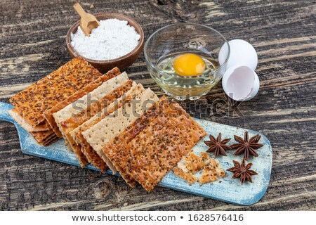 Stack of various organic crispy wheat flatbread crackers with sesame and salt on wooden background. Stock photo © DenisMArt
