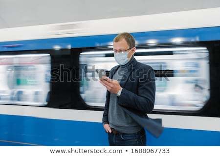 Photo of man in eyewear and protective medical mask, uses modern phone, travels by public transport, Stock photo © vkstudio