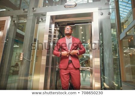 Iş adamı takım elbise çıkmak çekici gülen Stok fotoğraf © scheriton