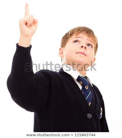 schoolboy in his uniform points upwards stock photo © annakazimir