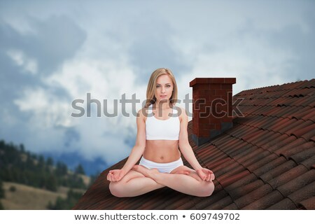 Portrait of young woman sitting in lotus position with eyes clos stock photo © wavebreak_media