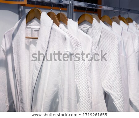 Bathrobes hanging on wooden hangers in wardrobe Stock photo © punsayaporn