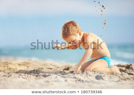 happy young boy is digging in the sand of the beach Stock photo © meinzahn