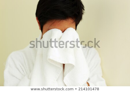 Young man in bathrobe wiping face with a towel Stock photo © deandrobot