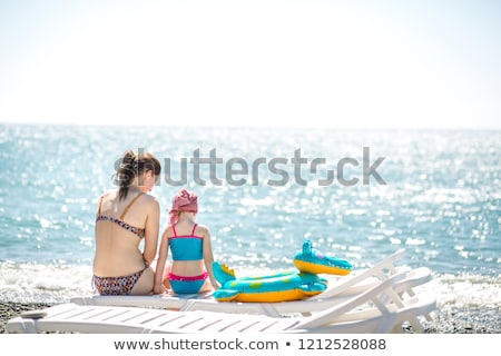 Mother with daughter on pebble in swimwear Stock photo © Paha_L
