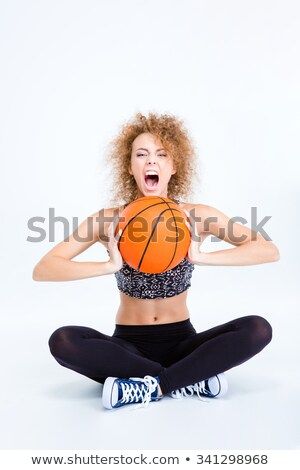 woman sitting on the floor with basketball ball and screaming stock photo © deandrobot