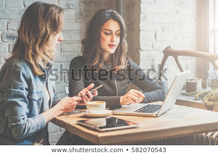 busineswoman talking on cell phone and using tablet in cafe stock photo © deandrobot
