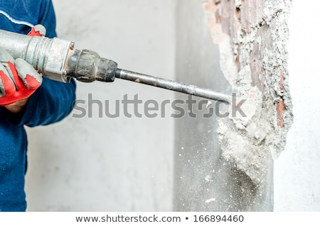 man using a jackhammer to drill into wall professional worker i stock photo © zurijeta