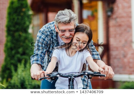 Grandfather teaching his granddaughter how to ride a bicycle Stock photo © wavebreak_media