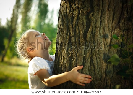 Happy little girl hugging tree trunk on a sunny day in the forest Stock photo © wavebreak_media