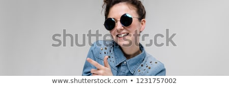 Young brunette girl in round glasses. Hairs are gathered in a bun. The girl points with her fingers. Stock photo © Traimak