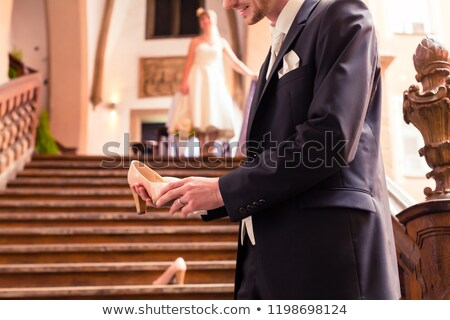 Smiling bridegroom holding high heel in his hand Stock photo © Kzenon
