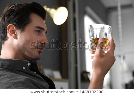 Stock photo: alcoholic with glass drinking whiskey at home