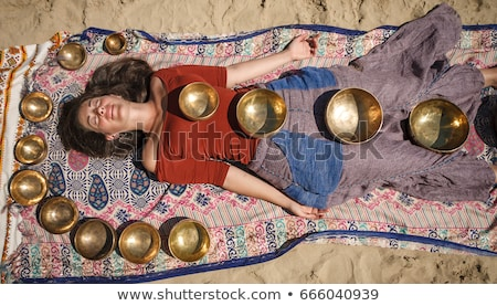Woman relaxing in spa with singing bowls on her body Stock photo © Kzenon