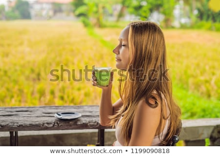 Young woman holding cup of matcha Latte, Green Tea, on old Woode Stock photo © galitskaya