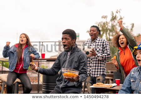 Multi-ethnic group of ecstatic youth with snack shouting during broadcast Stock photo © pressmaster