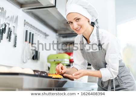 Pastry chef putting cranberries on top of little tartelettes Stock photo © Kzenon