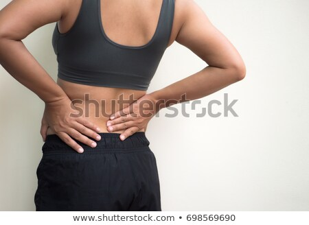 Fitness woman suffering from back pain Stock photo © Lopolo