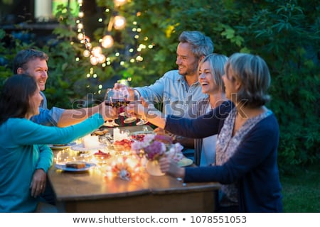 happy friends clinking drinks at home in evening Stock photo © dolgachov