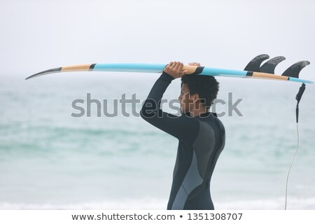 Side view of young mixed-race male surfer carrying surfboard on her head at beach Stock photo © wavebreak_media