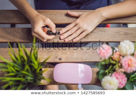 Young woman makes manicure with gel polish and UV lamp in pink shades Stock photo © galitskaya