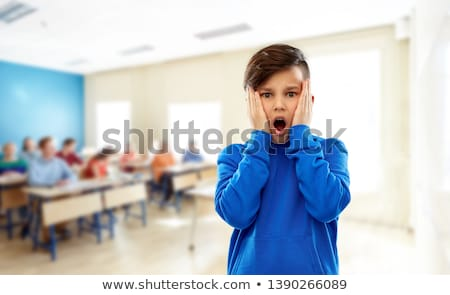 shocked or terrified boy touching face at school Stock photo © dolgachov
