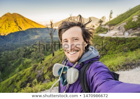 Young man tourist makes a selfie with the magnificent views on green mountains from a mountain road  Stock photo © galitskaya