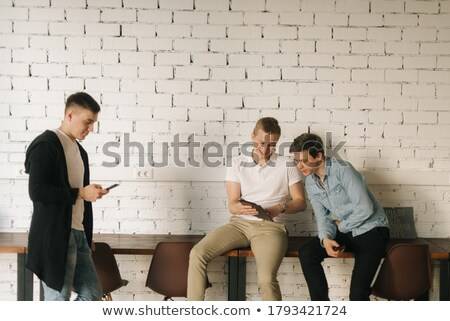 Team of people in startup company standing on brick wall Stock photo © Kzenon