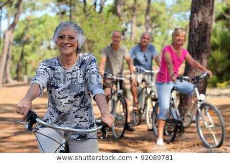 senior woman and her friends riding bikes through the countryside stock photo © photography33