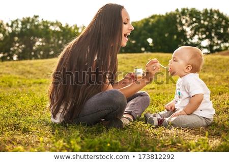 fiatal · gyönyörű · anya · etetés · baba · kint - stock fotó © dmitrydenisov
