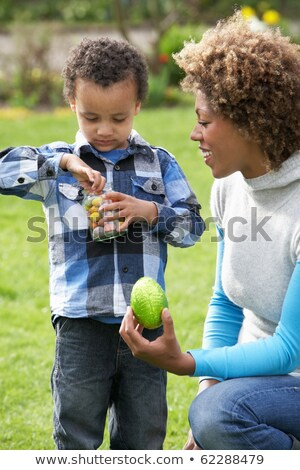 Mother Helping Son To Unwrap Chocolate Easter Egg Stock photo © monkey_business