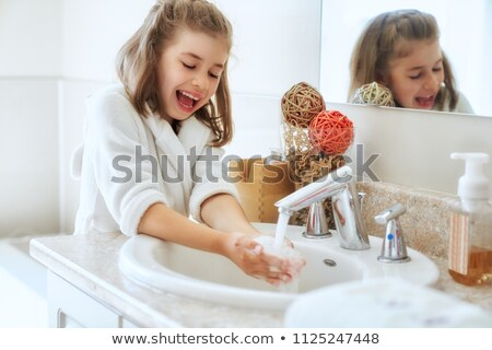 young woman in bathroom running water stock photo © dash