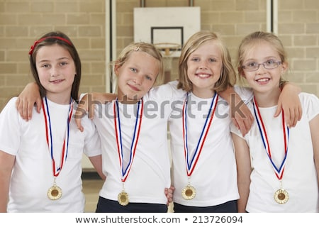 Female School Sports Team In Gym With Medals Stock photo © HighwayStarz
