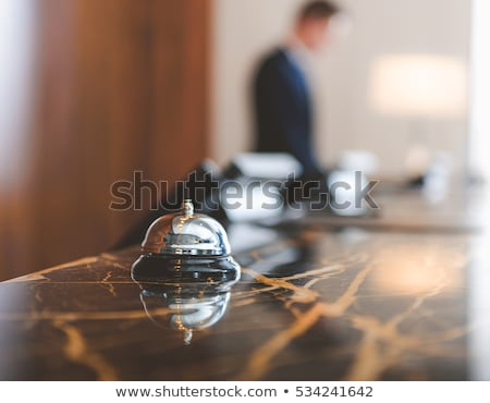 Man ringing hotel service bell on reception desk Stock photo © stevanovicigor