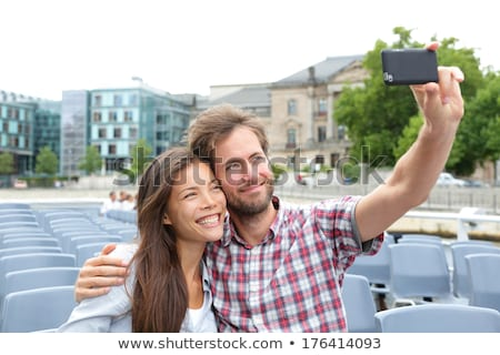 Stock photo: Beautiful couple taking a photo on a sailing boat at summer
