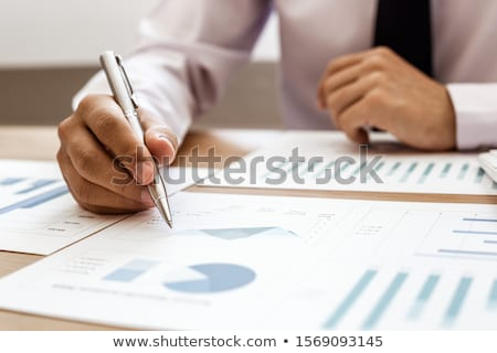 A man at the table with a pen and a paper with a graph Stock photo © bluering