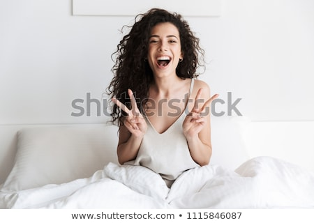 cheerful beautiful young woman relaxing on bed in bedroom stock photo © deandrobot