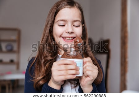 Little girl eating chocolate spread from jar and having fun Stock photo © deandrobot