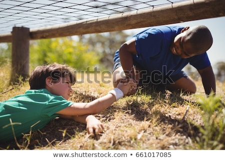 Boy crawling under the net during obstacle course training Stock photo © wavebreak_media
