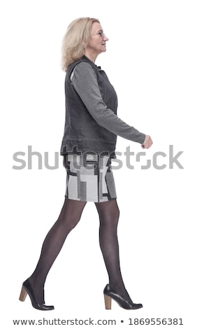 Stock photo: side view of a young woman in dress stepping forward
